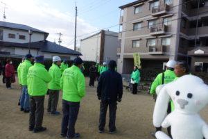 緑の上着を着た地域の方々が集まって説明を聞いています