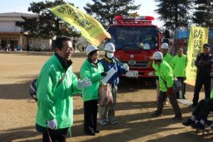 校庭に消防車が来ています。その前でヘルメットをかぶった人達が集まり挨拶をしています