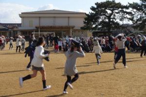 子ども達が頭に座布団を置きながら走って校庭に避難してきました