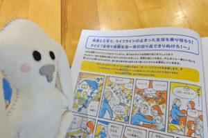 まちキョンが、大阪ガスの人が配った地震の冊子を見ています