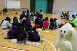 体育館に広がり子ども達がグループに分かれて話し合っています。その様子をまちキョンが見ています