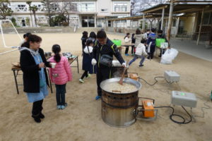 体育館の前の校庭で豚汁を作っています。炊き出し用の大きな寸胴鍋いっぱいの豚汁を地域の方がかき混ぜています