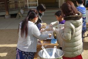長机の上で、地域の方々と子ども達が炊けたアルファ化米のご飯をパックに詰めています