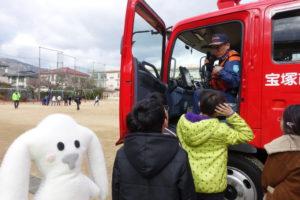 子ども達が消防士さんから消防車の運転席側にある装置の説明を聞いています