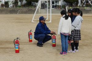 3人の女の子達が消防士さんから消火器の使い方の説明を受けています