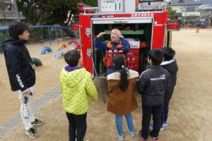 子ども達が消防士さんから、消防車の後ろにある装置の説明を聞いています