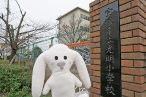 宝塚市立光明小学校の校門前にまちキョンが立っています
