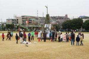 準備中の竹のやぐらのまわりに人が集まり見守っています