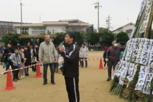 竹のやぐらの側で校長先生がマイクを持って挨拶をされています