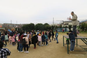 コミュニティ会長の田村さんが朝礼台の上から○×クイズを出題しています。子ども達がたくさん朝礼台前に集まっています