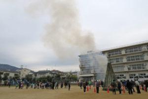 校庭の中央にあるやぐらから白い煙が空まで登っていっています。たくさんの人達がそれを見守っています