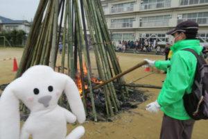 竹のやぐらは火が消え始めました。地域の方がやぐらの中にあるさつまいもの様子を木の棒で見ています