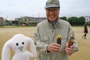 コミュニティ会長の田村さんが出来立てのさつまいもを半分に割って持っています。そのお隣にまちキョンがいます