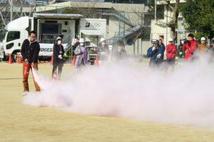 消防士さんの指示のもと、代表の人が消火器で火を消しています。白い煙が火を覆いました
