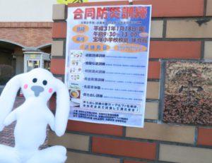 宝塚小学校校門前に合同防災訓練のポスターが貼ってあります。その前にまちキョンが到着しました