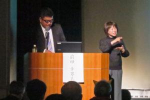 事例発表で舞台上にいる、はなみずき保育園園長の前田先生と手話通訳の方。