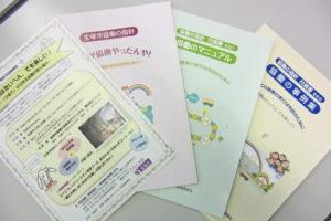 テーブルの上に説明会のチラシ、冊子「協働の指針」「協働のマニュアル」「協働の事例集」が置かれている。