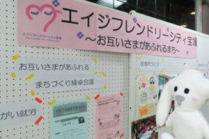 エイジフレンドリーシティ宝塚のブースには「お互いさまがあふれる」「まちづくり縁卓会議」などの言葉が書かれた紙やチラシが貼られ、案内パネルの前で写るまちキョン。