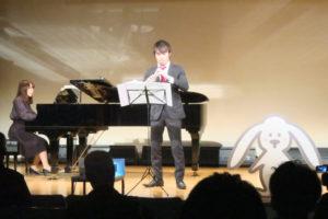 舞台上で女性がピアノ、男性がオーボエで一緒に演奏している。