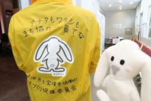 「アナタもワタシもまち協の会員です」と背中に大きく書かれた黄色いジャンパー。そのジャンパー着た運営の方と写るまちキョン。