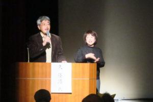 舞台上で講演する、近畿大学総合社会学部教授の久先生と手話通訳の方。