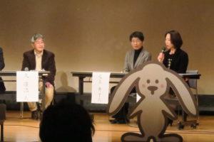 仁川小学校PTAの放課後遊ぼう会委員会委員長の三浦さんのトーク。その横には、足立さんと久先生が写っている。