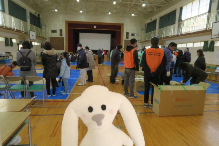 防災訓練の会場である安倉小学校の体育館の中に入ったまちキョン。その後ろにはすでに何人かの人が集まって、始まるのを待っている。