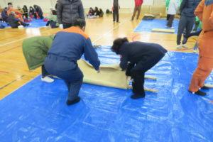 搬送訓練のコーナー。ブルーシートの上で、指導を受けながら、2本の竹の棒と毛布で担架を作る体験をする2人の女性。