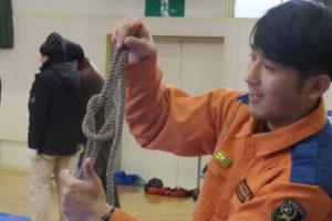 三角巾の使い方コーナー。ロープを使って「本結び」という結び方の手本を見せている男性。