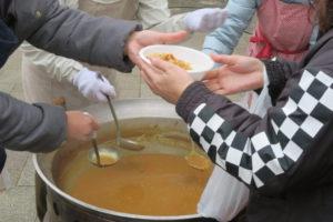 体育館の前での炊き出しの様子。大きなカレー鍋と、お椀にカレーを注ぐ人、受け取る人の手元のアップ。