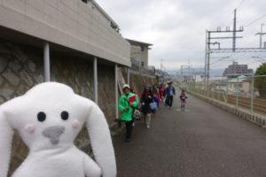塔の町会館を出発し、線路沿いの道を南へ進む参加者のみなさん。まちキョンは、その先頭を歩いている。