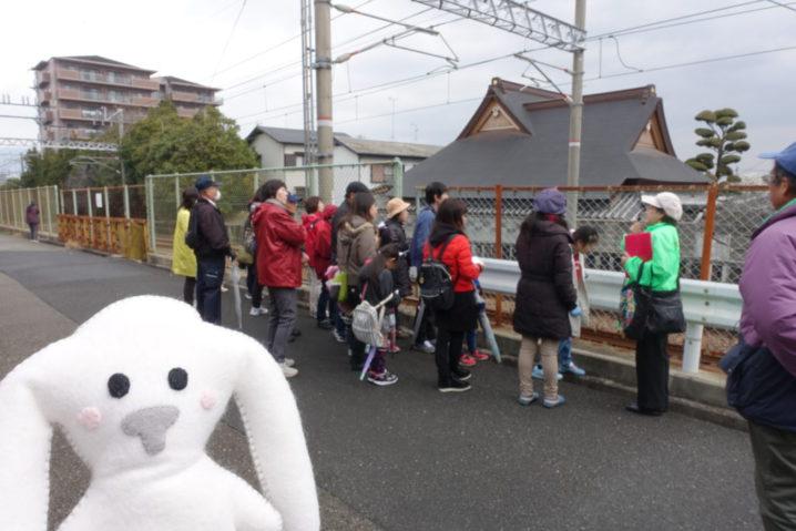 幻の駅「鹿塩駅」があったあたりへ、みんな到着。まちキョンのうしろでは、ガイドさんのお話を聞く参加者のみんなの姿がある。