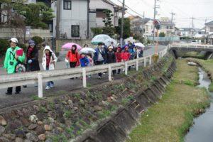 小仁川沿いの道を歩く参加者。少し雨が降ってきた様子でみんな傘をさし始めている。