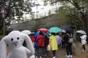 小林聖心女子学院の校門前でお話を聞く参加者。手前には、アップでまちキョンが映っている。