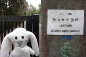 小林聖心女子学院の校門前にまちキョンがいる。