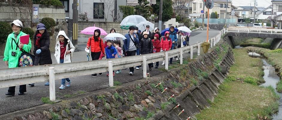 明るい緑のジャケットを着た人を先頭に、大人と子供が十数人くらい、川沿いを傘をさしながら一緒に歩いている