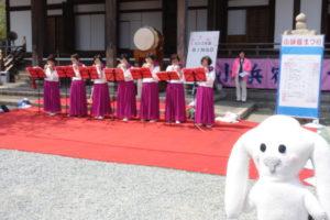 緋毛氈を敷いたステージ上で、お揃いの衣装を身に付けた7名の出演者たちがオカリナ演奏が披露しています。少し離れたところにまちキョンが立って見ています。