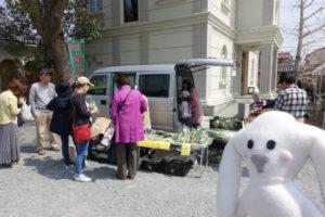 毫摂寺の境内の洋館のような建物「開基堂」の横では、西谷の新鮮なお野菜を運んで来たトラックがとまっています。その周りにお野菜が並べられていて、人が集まっています。少し離れたところにまちキョンが立ってその様子を眺めています。