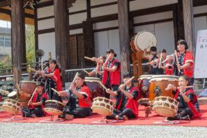 元気な和太鼓集団「熟光(ひかり)」のみなさんが大きな太鼓や小さな太鼓で力強く演奏しています。お揃いの赤い法被姿で元気なみなさんです。
