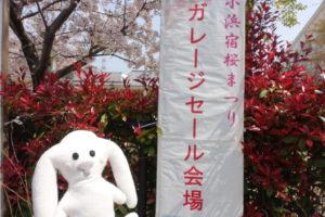 小浜小学校の運動場にやってきました。ここは、小浜宿桜まつりのガレージセールの会場になっています。「小浜宿桜まつりのガレージセール」と書かれた垂れ幕の前にまちキョンが立っています。