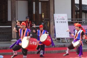 ステージの上で、大太鼓や締太鼓をたたいて沖縄エイサーを演じる若者たち。大太鼓にはレキオと書かれています。