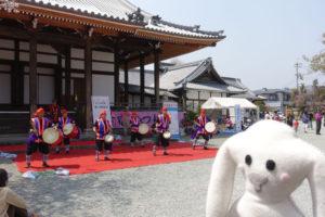 ステージの上で、太鼓を抱えて沖縄エイサーを踊る若者たちが写っています。少し離れたところからまちキョンがその演奏と踊りを眺めています。