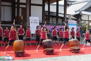 ステージで、山口子ども太鼓クラブの子どもたちが「祭」を演奏しています。前に大太鼓を並べて、大きく手をあげて太鼓を打とうとしています。
