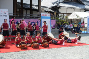 ステージで、山口子ども太鼓クラブの子どもたちが演奏しています。後ろに並ぶ子どもたちは大きな声で歌っています。前に並ぶ子たちは、大太鼓や締太鼓をたたいています。