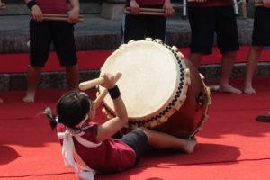 ステージ上で、山口子ども太鼓クラブの大太鼓を打つ子どものアップ写真です。ステージに仰向けに寝て、大太鼓を足の膝から下で支え、上半身を半分持ち上げるような姿勢で、力強く大太鼓を打っています。