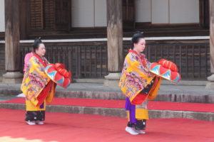 ステージの上で、沖縄の独特の衣装を着て、花笠を両手で前に持って、三線と沖縄民謡の歌声に合わせて琉球舞踊を踊っています。