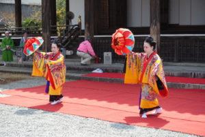 ステージの上で、沖縄舞踊を踊っています。沖縄の独特の衣装を着て、花笠を右手で持ち上げ、左手と左足を前に出しています。
