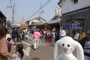 まちキョンが通りに出てきました。まちキョンの後ろにはパレードが近づいていて、パレードを多くの人が見にきています。