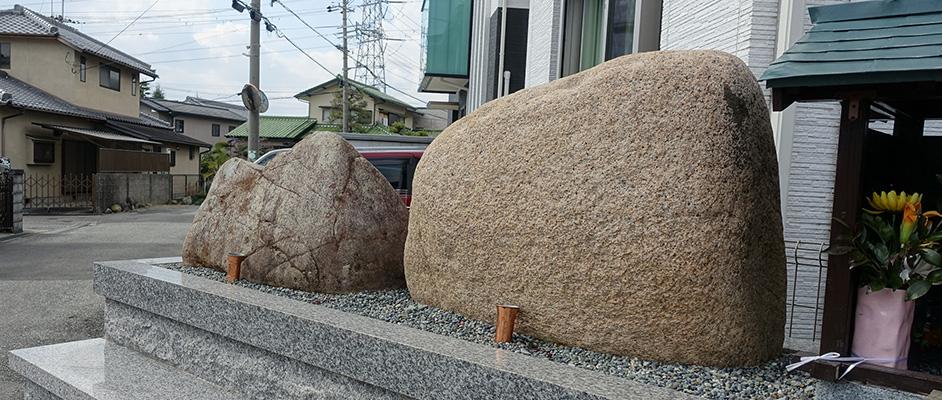 安倉地区にある、動かすと泣き出すという伝承のある2つの石が、綺麗に整備された場所に鎮座した様子が大きく写っている。背景に周辺のまち並みが見える