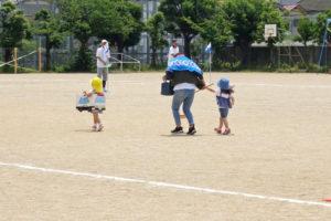 ザルの中に入った荷物を落とさないようにゴールを目指すゲーム 小さい子達もお母さんに手を引かれながら一生懸命に走っています